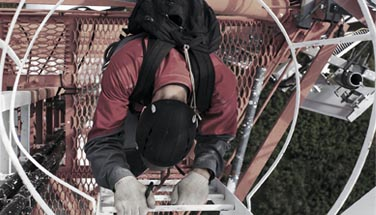 Technician climbing telecom tower